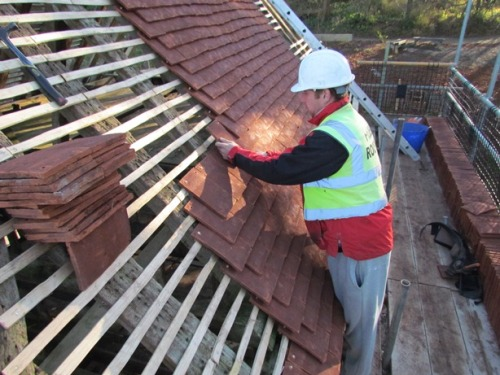 Heritage SAP candidate laying clay peg tiles on a roof at the Weald & Downland Open Air Museum